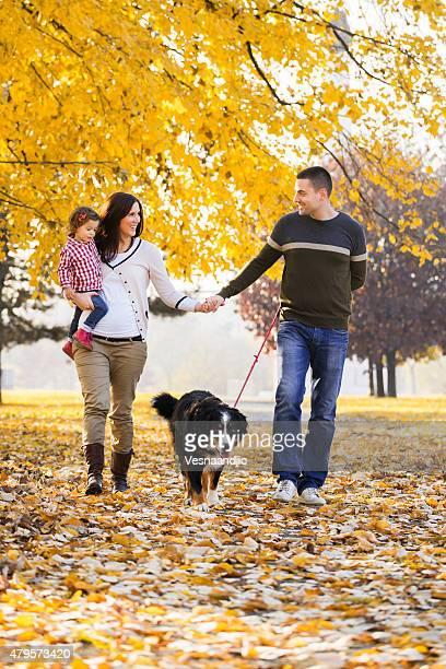 Fröhliche Familie mit Hund im Freien