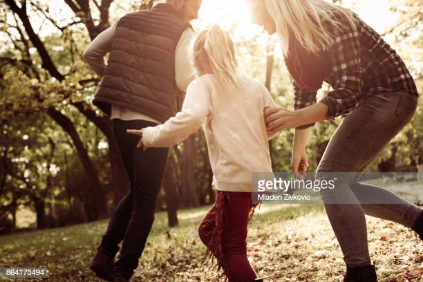 Cheerful family with one child playing together in park.