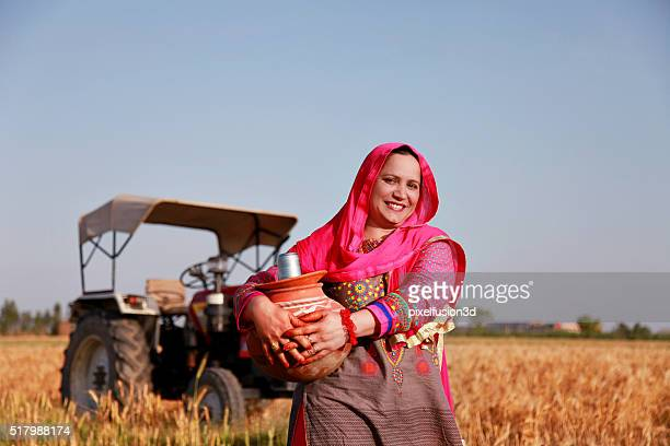 Cheerful Farmer women carrying water pot
