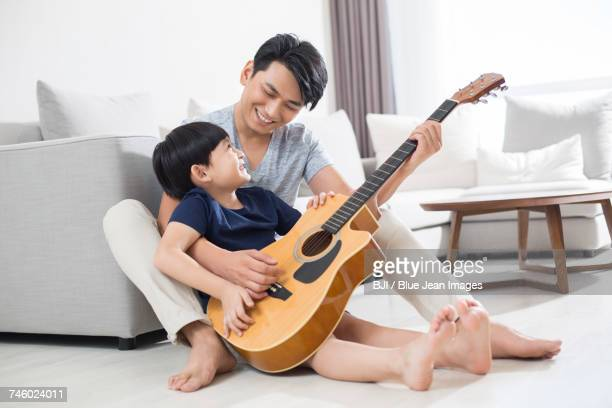 Cheerful father and son playing the guitar at home