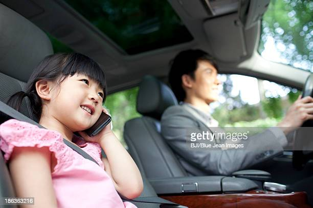 Cheerful father driving with daughter in front seat