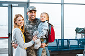 cheerful father in military uniform holding in arms cute daughter and standing near wife in airport