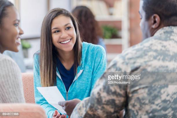 Cheerful female college students meet with military recruiter