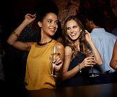 Cheerful female friends dancing in nightclub