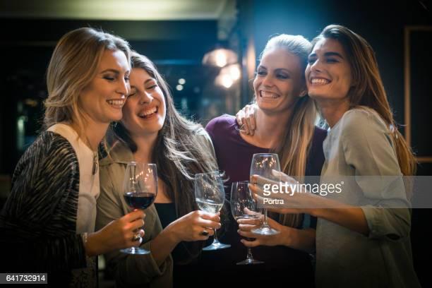 Cheerful female friends enjoying drinks in bar