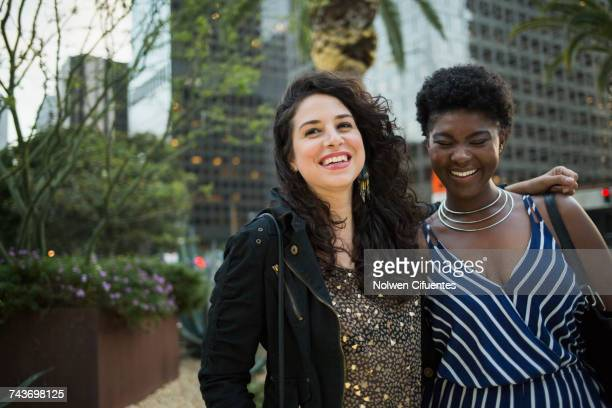 Cheerful female friends with arm around against building in city, Los Angeles, California, USA