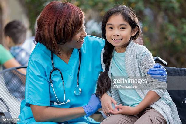 Cheerful female nurse hugs young patient at outdoor clinic