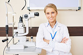 Portrait of blonde female ophthalmologist sitting at slit lamp machine while posing confidently with arms crossed and smiling happily
