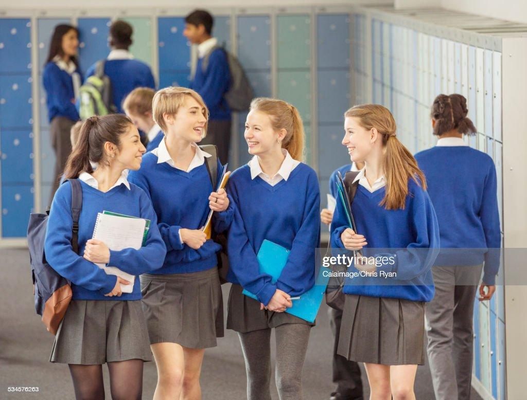 Cheerful female students wearing blue school uniforms walking in locker room