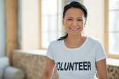 Service learning. Happy optimistic female volunteer posing on blurred background and grinning while gazing at camera