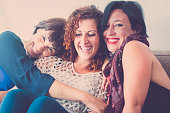 cheerful females middle age young womens friends together sitting on a sofa at home in leisure activity indoor. smile and enjoy the day hugging and touching with care and friendship