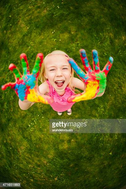 Cheerful finger painting girl in fisheye perspective