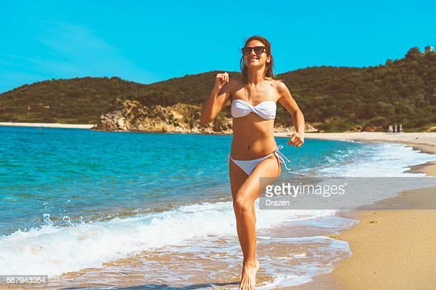 Cheerful fit girl in white bikini jogging on deserted beach