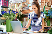 Cheerful florist looking at laptop and writing down client orders in notebook
