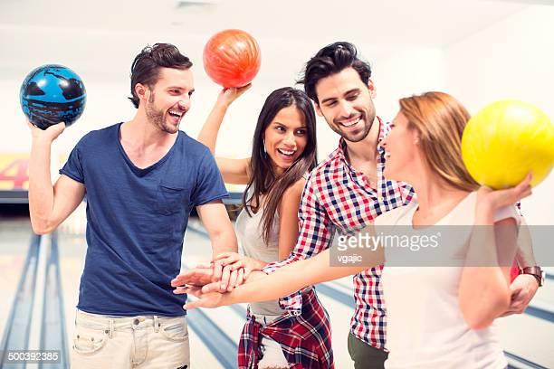 Alegres amigos Bowling em conjunto.