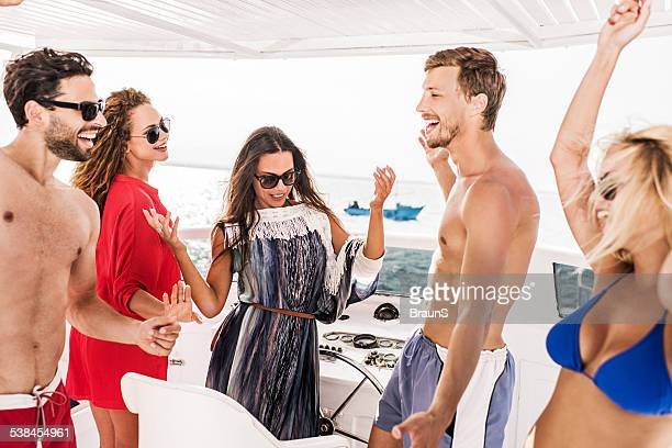 Cheerful friends dancing on a yacht.