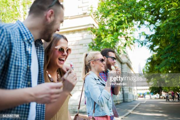 Cheerful friends eating ice cream and walking