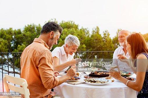 Cheerful friends enjoying dinner on terrace stock photo for Dinner on the terrace