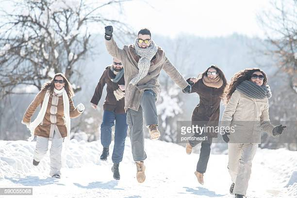 Cheerful friends having fun in the snow