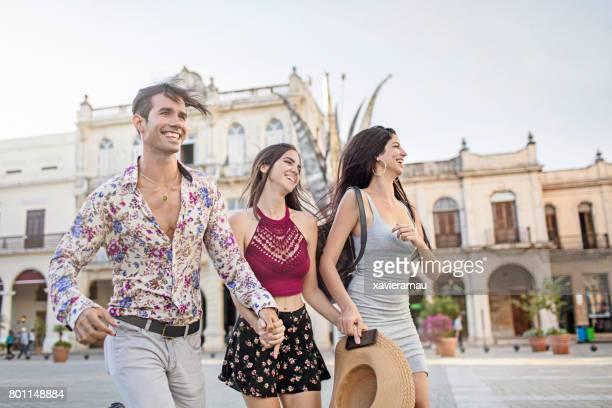 Fröhliche Freunde laufen am Stadtplatz in Havanna