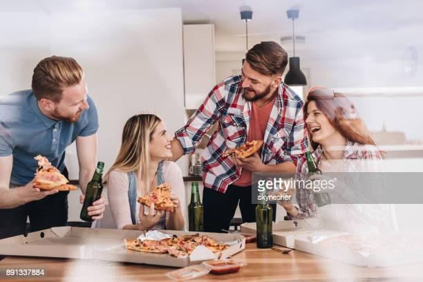 Glada vänner prata medan man äter pizza till lunch hemma.