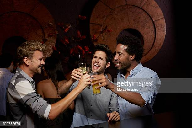 Cheerful friends toasting drinks in nightclub