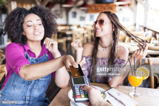 Cheerful friends using credit card in cafe