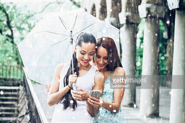 Cheerful friends using phone in the rain