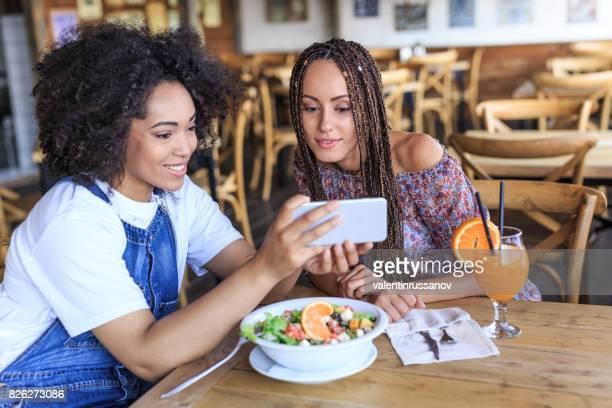 Alegre con sus amigos utilizando el teléfono inteligente en cafetería