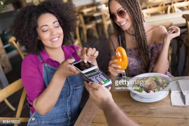 Amigos alegres utilizando teléfonos inteligentes para pagos móviles