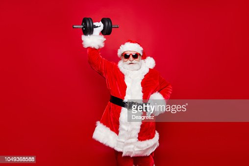 Cheerful funny trendy stylish fashionable strong sporty virile muscular Santa in eyeglasses gloves fur white red winter coat black belt lifting one big dumbbell striving isolated on red background : Foto de stock