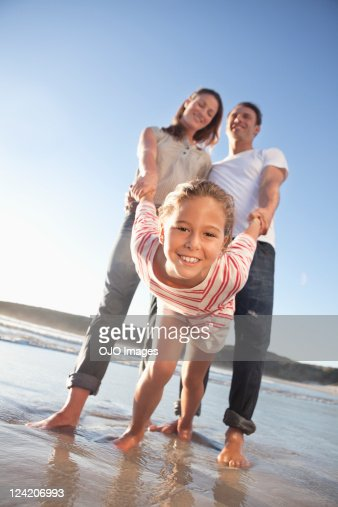 Cheerful girl enjoying at the beach with parents : Stock Photo