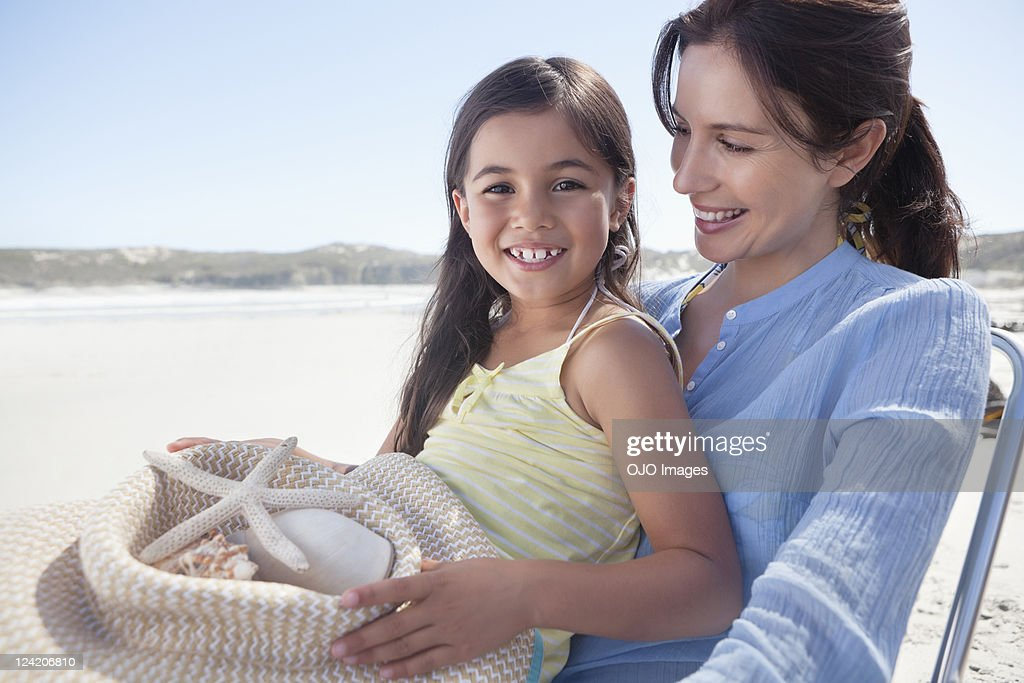 Cheerful girl enjoying on beach with mother holding starfish : Stock Photo