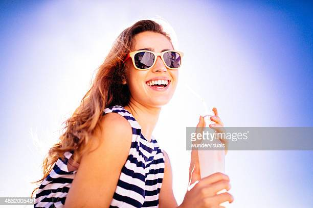 Cheerful girl having a cool drink