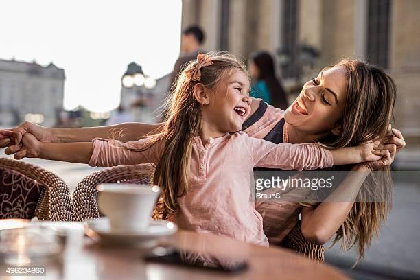 Joyeuse fille s'amuser avec sa jeune mère au café.