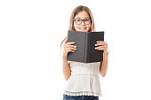Portrait of little adorable girl wearing white shirt and spectacles holding open book against white background
