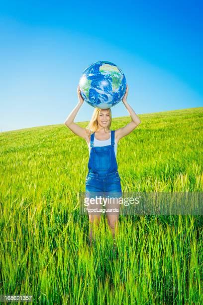 Fröhliche Mädchen hält eine Welt Globus