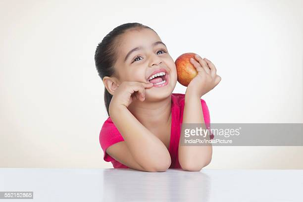 Cheerful girl holding fresh red apple against colored background