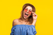 Portrait of young stylish model in sunglasses and straw hat posing expressively with mouth opened.