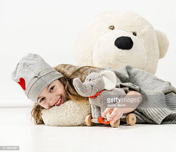 Cheerful girl is hugging elephant toy and huge teddy bear