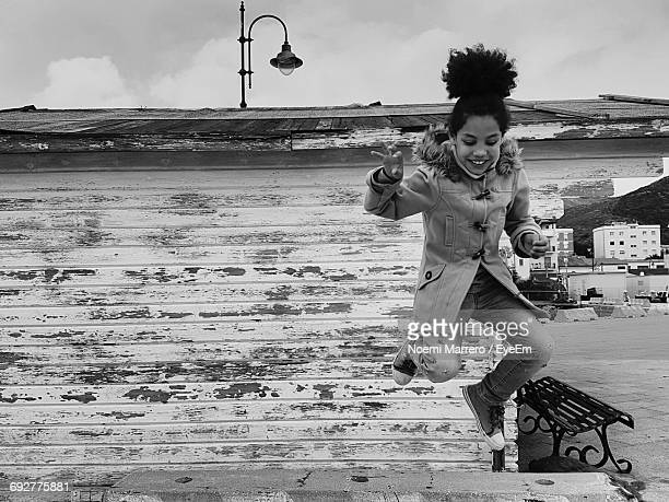 Cheerful Girl Jumping Against Hut