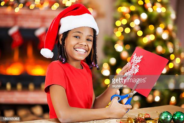 Cheerful girl making Christmas cards.