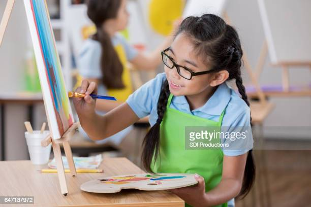 Cheerful girl paints in art class
