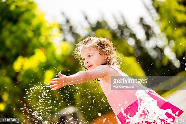 Cheerful girl splashing water with hand