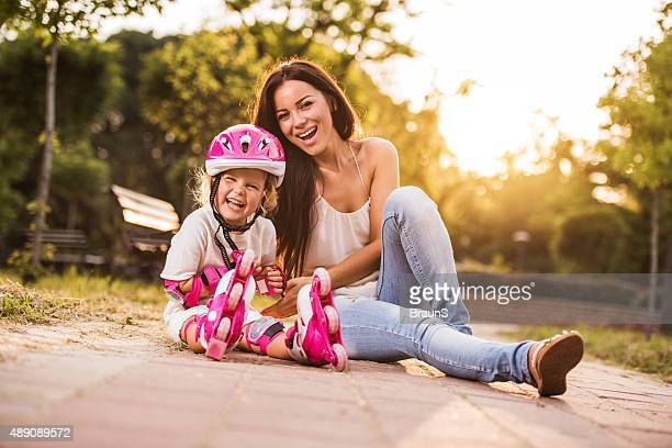 Cheerful girl with rollerblades and her young mother in nature.