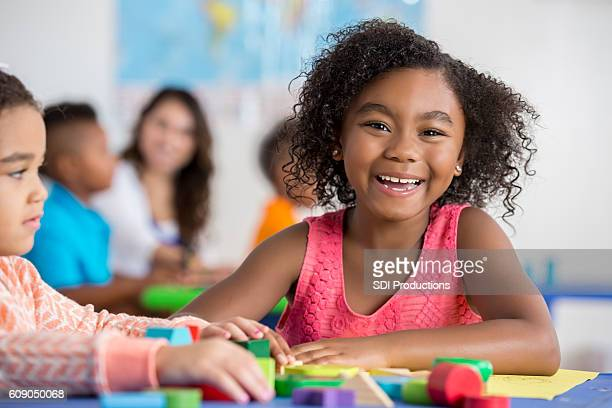 Cheerful girl works on project at school