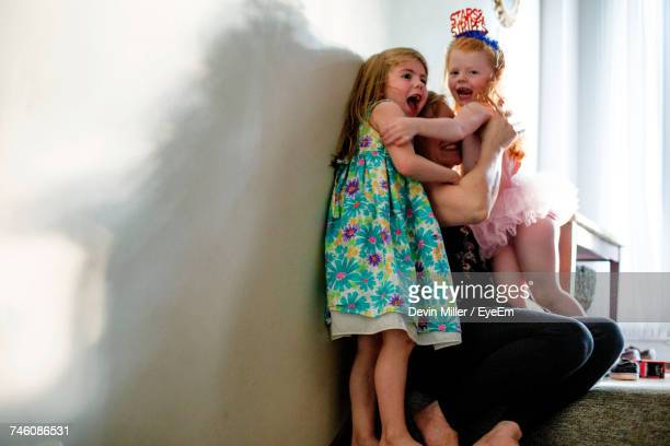 Cheerful Girls Embracing Mother Against Wall At Home