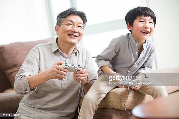Cheerful grandfather and grandson playing video game