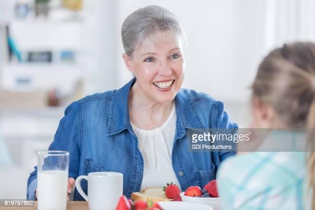 Cheerful grandma eats breakfast with granddaughter