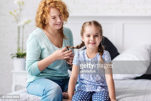Cheerful grandmother plaiting braids to her granddaughter : Stock Photo